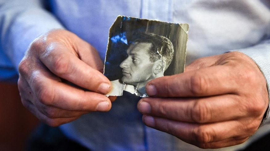 In this Dec. 3, 2015 photo, Uruguayan journalist Gerardo Bleier, holds a picture of his father Eduardo Bleier, who dissapeared during the Uruguayan dictatorship, in Montevideo, Uruguay. When Uruguay returned to democracy in 1985, then-President Julio Maria Sanguinetti appointed a military prosecutor to investigate claims of disappeared loved ones. Bleier says Sanguinetti mistakenly downplayed the military's violence. (AP Photo/Matilde Campodonico)