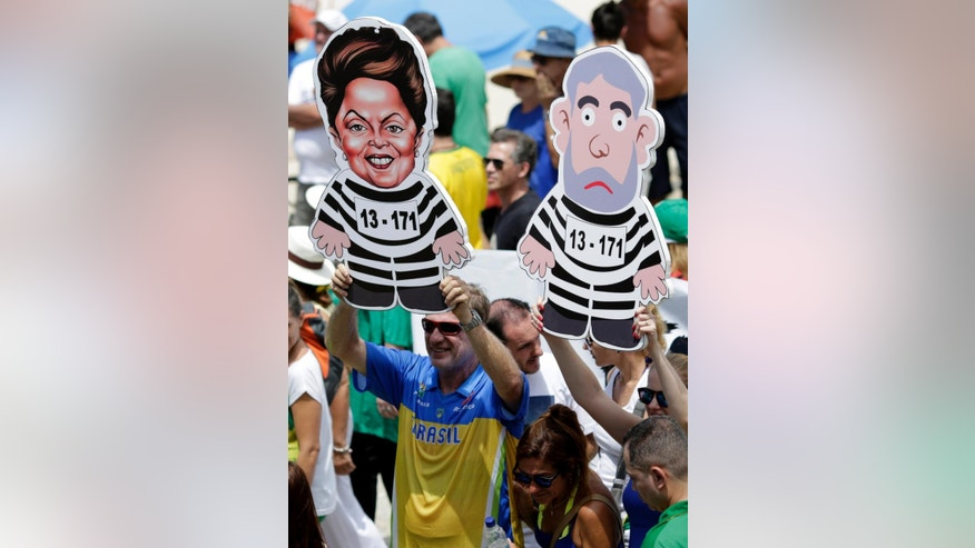 People hold  ikenesses of former Brazilian president Luiz Inacio Lula da Silva and Brazil's President Dilma Rousseff  in prison stripes during a demonstration for the impeachment of Rousseff on Copacabana beach, Rio de Janeiro, Brazil, Sunday, Dec. 13, 2015. Dozens of cities are staging protests across Brazil asking Congress to impeach President Dilma Rousseff. Hundreds have gathered Sunday in cities such as Brasilia, Rio de Janeiro and Sao Paulo wearing Brazil's national soccer jersey. They are holding banners that criticize the president and her Workers' Party for a massive corruption scandal at the state-run oil company.(AP Photo/Silvia Izquierdo)
