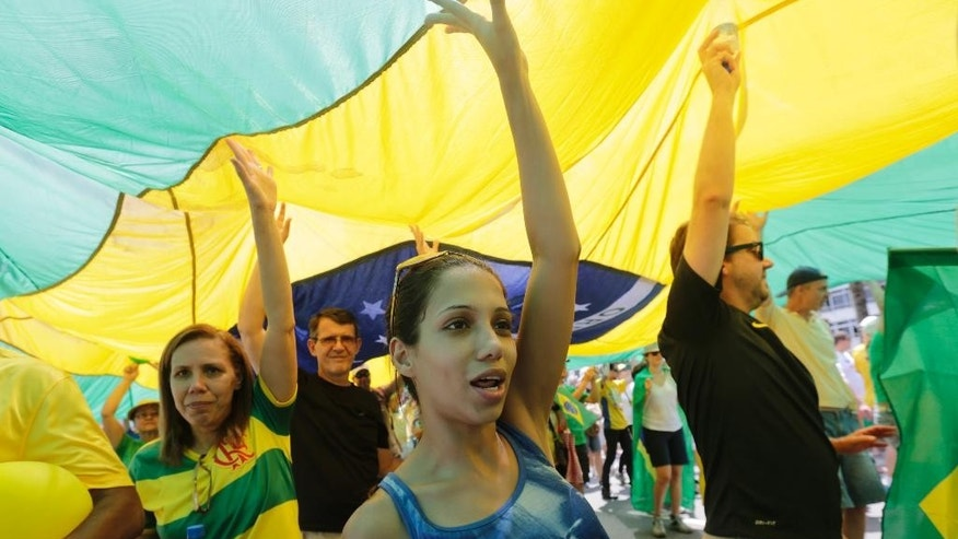 People holds a Brazilian flag during a demonstration for the impeachment of Brazil's President Dilma Rousseff on Copacabana beach, Rio de Janeiro, Brazil, Sunday, Dec. 13, 2015. Dozens of cities are staging protests across Brazil asking Congress to impeach President Dilma Rousseff. Hundreds have gathered Sunday in cities such as Brasilia, Rio de Janeiro and Sao Paulo wearing Brazil's national soccer jersey. They are holding banners that criticize the president and her Workers' Party for a massive corruption scandal at the state-run oil company.(AP Photo/Silvia Izquierdo)