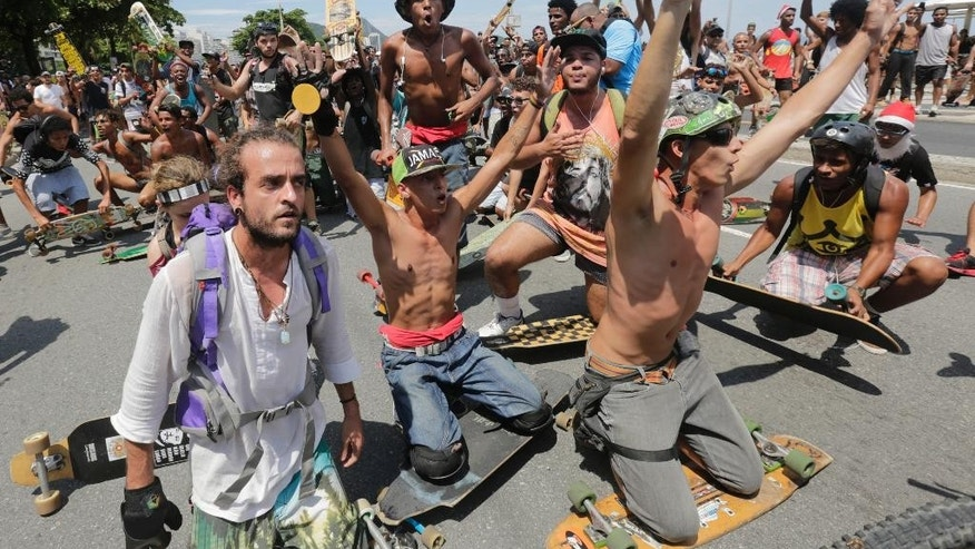 Skateboarders argue with demonstrators during a march for the impeachment of Brazil's President Dilma Rousseff  on Copacabana beach, in Rio de Janeiro, Brazil, Sunday, Dec. 13, 2015. The demonstrations are organized by the same right-leaning groups that produced massive turnouts earlier this year to demand Rousseff's impeachment when the process hadn't started. (AP Photo/Silvia Izquierdo)