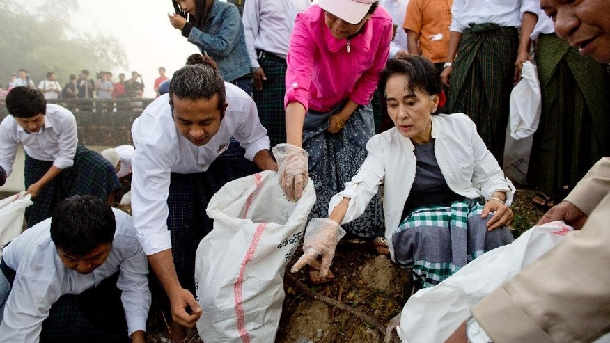 Leader of National League for Democracy party (NLD) Aung San Suu Kyi, center right, points at garbage during a clean-up drive initiated by Suu Kyi in Kawhmu, Myanmar Sunday, Dec. 13, 2015. Suu Kyi lead the garbage collection on early foggy Sunday in Kawhmu township of Yangon region, where she won her seat for the Lower House in the country's general election. (AP Photo/Gemunu Amarasinghe)
