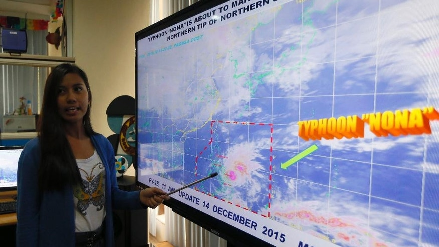 Government weather forecaster Loriedin De La Cruz briefs the media on Typhoon Melor at the weather bureau center in suburban Quezon city, northeast of Manila as it hits the eastern Philippines Monday, Dec. 14, 2015. Thousands of residents evacuated as the typhoon slammed into the eastern Philippines, where flood- and landslide-prone communities are bracing for destructive winds, heavy rains and coastal floods of up to 4 meters (13 feet), officials said Monday. (AP Photo/Bullit Marquez)