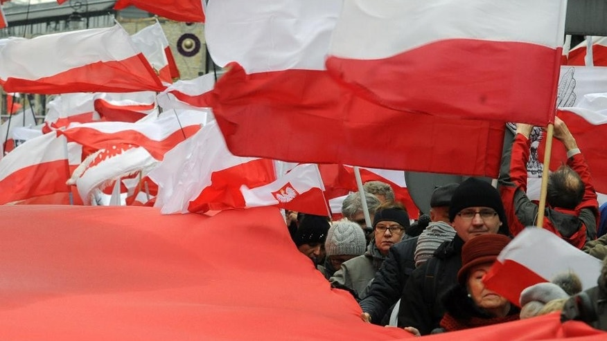 Thousands of backers of Poland's ruling conservative party wave national  flags as they march with the party leader to show their support for its policy amid a growing political conflict, in Warsaw, Poland, Sunday, Dec. 13, 2015. The march, led by Law and Justice party head Jaroslaw Kaczynski, comes a day after tens of thousands of government opponents demonstrated in Warsaw and elsewhere, saying the ruling party and President Andrzej Duda are threatening democracy. (AP Photo/Alik Keplicz)