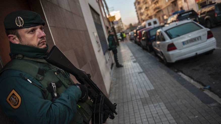 Spanish Civil Guard stand near a tea shop center, right, where they detained an unidentified man of Morocco, in Pamplona, northern Spain, Tuesday, Dec.1, 2015.  Spanish authorities allege the man is a suspected member of a cell that recruited jihadi fighters for the Islamic State group in Syria. (AP Photo/Alvaro Barrientos)