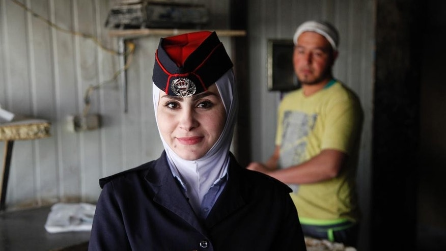 Abeer Mohammed, a community police officer stands for a portrait inside a bakery in Zaatari refugee camp, Jordan, Monday, Dec. 14, 2015. Community police have begun patrolling the alleys of Jordan's two main camps for Syrian refugees, hearing grievances and trying to spot problems. The new police assistants are retired Jordanian officers trained in a British Embassy program.  (AP Photo/Sam McNeil)