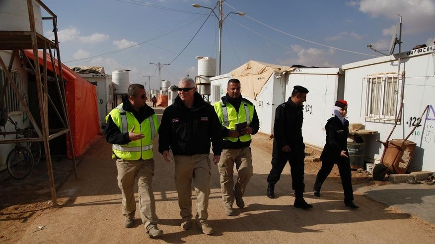 ?A new community police patrol walks down a road in Zaatari refugee camp, Jordan, Monday, Dec. 14, 2015. Community police have begun patrolling the alleys of Jordan's two main camps for Syrian refugees, hearing grievances and trying to spot problems. The new police assistants are retired Jordanian officers trained in a British Embassy program.  (AP Photo/Sam McNeil)