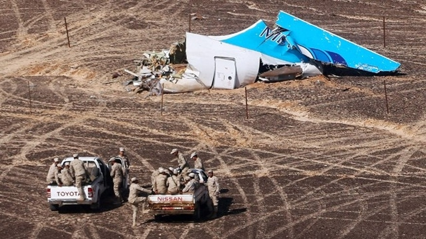 FILE - In this Sunday, Nov. 1, 2015 photo provided by Russian Emergency Situations Ministry, Egyptian Military on cars approach a plane's tail at the wreckage of a passenger jet bound for St. Petersburg in Russia that crashed in Hassana, Egypt. (Maxim Grigoriev/Russian Ministry for Emergency Situations via AP, File)