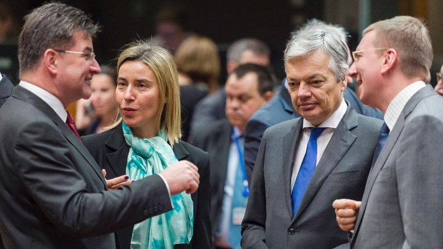 EU foreign police chief Federica Mogherini, 2nd left, talks with Slovakia's Foreign Minister Miroslav Lajcak, left, while Latvia's Foreign Minister Edgars Rinkevics, right, talks with Belgium's Foreign Minister Didier Reynders during an EU foreign ministers meeting at the EU Council building in Brussels Monday, Dec. 14, 2015. (AP Photo/Geert Vanden Wijngaert)