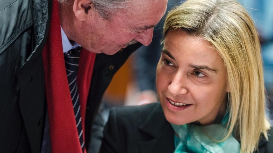 Luxembourg's Foreign Minister Jean Asselborn, left, talks with EU foreign policy chief Federica Mogherini during an EU foreign ministers meeting at the EU Council building in Brussels Monday, Dec. 14, 2015. (AP Photo/Geert Vanden Wijngaert)