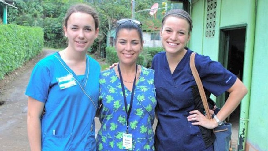 In this June, 2014 photo, U.S. citizen Sondra Lynn, center, poses with unidentified fellow volunteers in Costa Rica. Lynn, who organized volunteer medical missions in Central America, was found stabbed to death on Thursday, Dec. 10, 2015, in the capital of Costa Rica. Police say her body was found on a bed at a San Jose hotel. (Vida Volunteer Travel via AP)