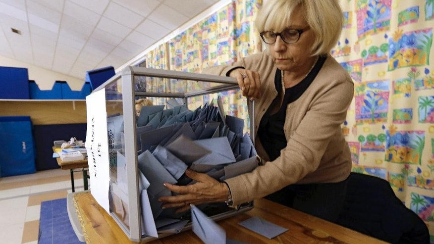 A worker empties a ballot box before counting ballots in the regional elections, Sunday, Dec. 13, 2015, in Nice, southeastern France. Far-right National Front party collapsed in French regional elections Sunday after dominating the first round of voting, according to pollsters' projections.(AP Photo/Lionel Cironneau)