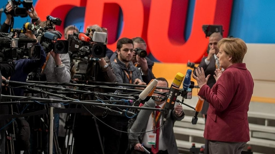 Christian Democratic Party , CDU, chairwoman and German  Chancellor,  Angela Merkel ,  speaks to reporters during preparations for the  CDU party convention in Karlsruhe, Germany, Sunday Dec. 13,  2015.  (Michael Kappeler/dpa via AP)