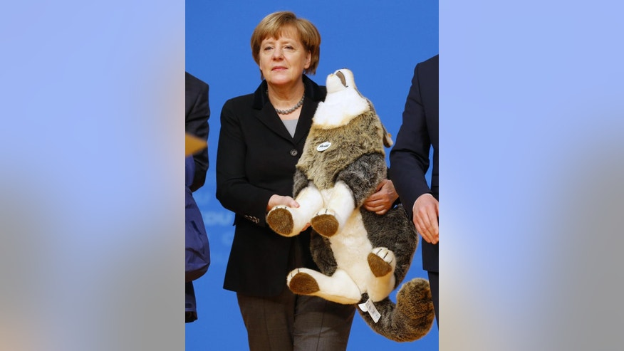 German Chancellor Angela Merkel holds a toy wolf she got as a present during a party convention of the Christian Democrats (CDU) in Karlsruhe, Germany, Monday, Dec. 14, 2015.   Merkel faces a congress of her conservative party amid tensions over her management of the migrant influx. (AP Photo/Michael Probst)