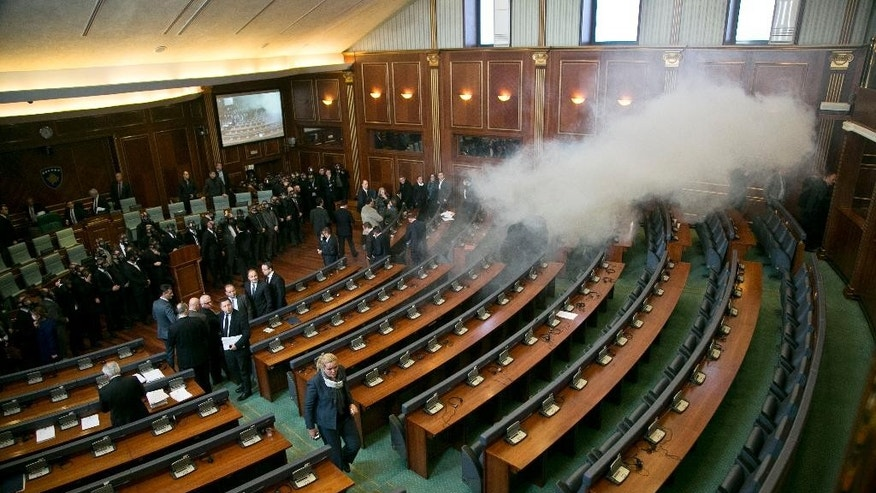 Smoke fills the auditorium of the Kosovo assembly after opposition lawmakers released tear gas canisters disrupting a parliamentary session in Kosovo capital Pristina on Monday Dec. 14, 2015. Opposition lawmakers have released tear gas in Kosovo's parliament in their latest attempt to pressure the government into renouncing deals with Serbia and Montenegro.  Clouds of smoke at the debating chamber released from two smuggled tear gas canisters forced lawmakers out of parliament Monday, something the opposition has successfully achieved since mid-September also using pepper spray, whistles and water bottles.  (AP Photo/Visar Kryeziu)