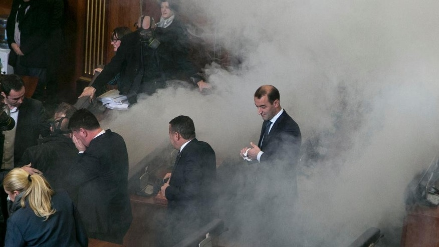 Lawmakers react as opposition lawmakers release tear gas canisters disrupting a parliamentary session in Kosovo capital Pristina on Monday Dec. 14, 2015. Opposition lawmakers have released tear gas in Kosovo's parliament in their latest attempt to pressure the government into renouncing deals with Serbia and Montenegro.  Clouds of smoke at the debating chamber released from two smuggled tear gas canisters forced lawmakers out of parliament Monday, something the opposition has successfully achieved since mid-September also using pepper spray, whistles and water bottles.  (AP Photo/Visar Kryeziu)