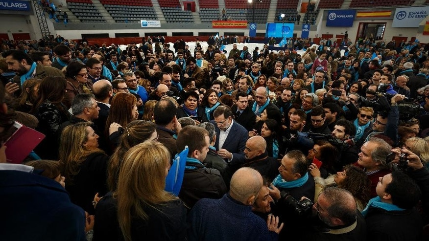 Supporters of Spain's Prime Minister and right wing Popular Party candidate Mariano Rajoy, center, try to get close to him during a campaign rally at Las Rozas bullring, near Madrid, Spain, Sunday, Dec. 13, 2015 . The Spanish general elections will be held on Sunday, Dec. 20.(AP Photo/Daniel Ochoa de Olza)