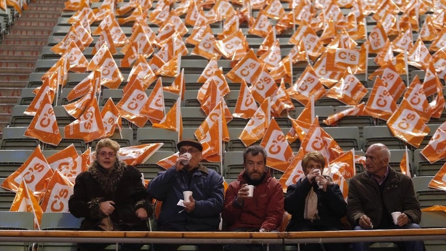 In this Sunday, Dec. 13, 2015, photo, people drink hot chocolate as they wait for the start of a campaign rally of Ciudadanos party in Madrid, Spain. Polls show Prime Minister Mariano Rajoy's Popular Party set to win the most votes, but falling far short of the tally needed to retain the majority it holds in Parliament, meaning it would have to ally with another party, most likely Ciudadanos. Another possibility would be a matchup between the Socialists and Podemos. (AP Photo/Francisco Seco)