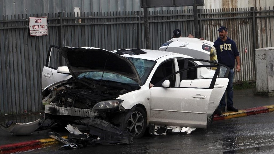 Israeli police examine a car used in a vehicular attack in Jerusalem Monday, Dec. 14, 2015. A Palestinian rammed his car into a bus station wounding nine people before he was shot and killed by bystanders, police said. (AP Photo/Mahmoud Illean)