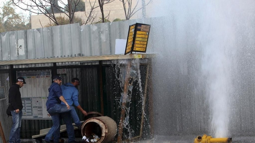 Israeli policemen push a trash container, as water sprays from a burst fire hydrant, at a scene of an attack in Jerusalem Monday, Dec. 14, 2015. A Palestinian rammed his car into a bus station wounding nine people before he was shot and killed by bystanders, police said. (AP Photo/Mahmoud Illean)
