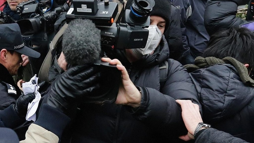 Policemen try to stop a foreign video journalist covering rights lawyer Pu Zhiqiang's trial near the Beijing Second Intermediate People's Court in Beijing, Monday, Dec. 14, 2015. Police scuffled with protesters and journalists at the Beijing courthouse Monday as the prominent lawyer stood trial on charges of provoking trouble and stirring ethnic hatred with online commentary critical of the ruling Communist Party. (AP Photo/Andy Wong)