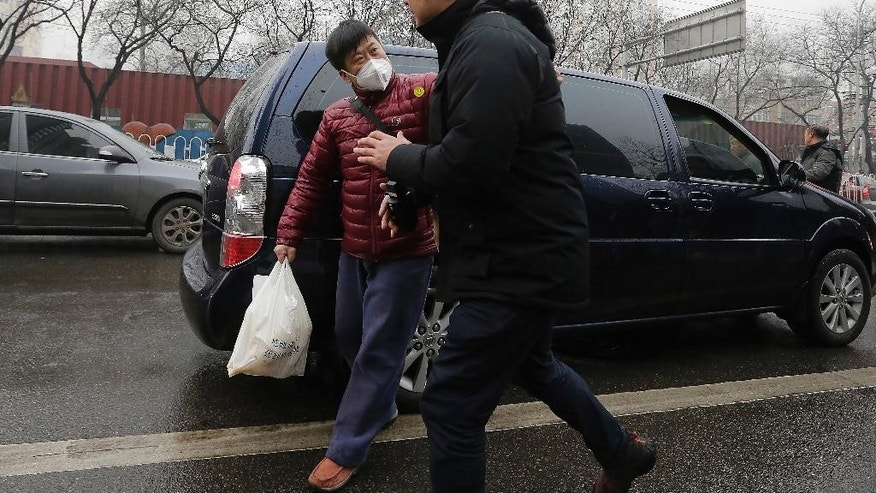 A plainclothes policeman, left, pushes away a foreign journalist covering rights lawyer Pu Zhiqiang's trial near the Beijing Second Intermediate People's Court in Beijing, Monday, Dec. 14, 2015. Pu went on trial Monday on charges of provoking trouble with commentaries on social media that were critical of the ruling Communist Party. (AP Photo/Andy Wong)