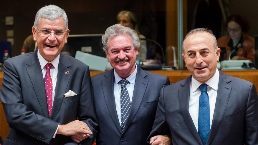 Turkey's European Affairs Minister Volkan Bozkir, left, and Foreign Minister Mevlut Cavusoglu, right, pose for photographers with Luxembourg's Foreign Minister Jean Asselborn during an EU Turkey Intergovernmental meeting at the EU Council building in Brussels on Monday, Dec. 14, 2015. (AP Photo/Geert Vanden Wijngaert)