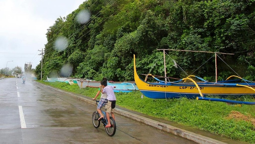 Boys pedal their way past boats placed on a safer area in Legazpi city, central Philippines as Typhoon Melor slammed into the eastern Philippines, Monday, Dec. 14, 2015. Hundreds of thousands of residents fled their homes as Typhoon Melor slammed into the eastern Philippines, where flood- and landslide-prone communities are bracing for destructive winds, heavy rains and coastal floods of up to 4 meters (13 feet), officials said Monday. (AP Photo/Roldano Amaranto)