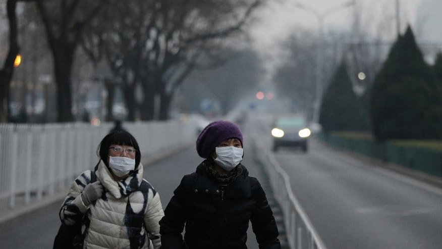 Women wear masks as they walk along a street on a polluted day in Beijing, Sunday, Dec. 13, 2015. China's push for a global climate pact is partly because of its own increasingly pressing need to solve serious environmental problems, observers said Sunday. (AP Photo/Andy Wong)