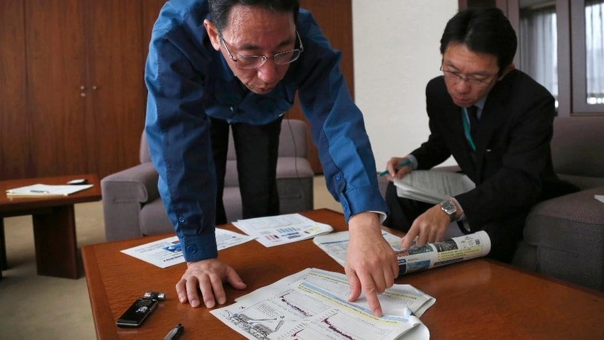 "In this Monday, Dec. 14, 2015 photo, Naohiro Masuda, left, chief of decontamination and decommissioning of the Fukushima Daiichi nuclear plant for its owner Tokyo Electric Power Co. (TEPCO), talks during an interview at the TEPCO headquarters in Tokyo. Masuda, the man leading the daunting task of dealing with the nuclear plant that sank into meltdowns in northeastern Japan, warns with surprising candor: Nothing can be promised. ""This is something that has never been experienced. A textbook doesn't exist for something like this,"" Masuda told The Associated Press. (AP Photo/Koji Ueda)"