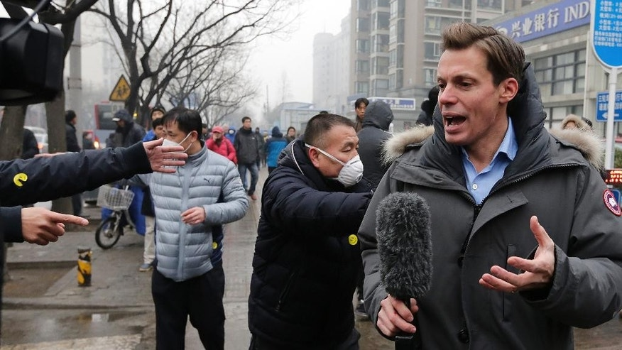 """In this Monday, Dec. 14, 2015, photo, a foreign journalist covering the trial of prominent rights lawyer Pu Zhiqiang is confronted by plainclothes policemen wearing yellow smiley-face stickers, near Beijing's No. 2 Intermediate Court in Beijing. The tough guys wore smiley face stickers, but they weren't there to spread good cheer. Scenes of pushing, shouting and shoving outside a Beijing courthouse this week were orchestrated by plainclothes security officers identified by a sticker familiar around the world — the yellow decal identified since the 1970s with the slogan """"Have a Nice Day."""" (AP Photo/Andy Wong)"""