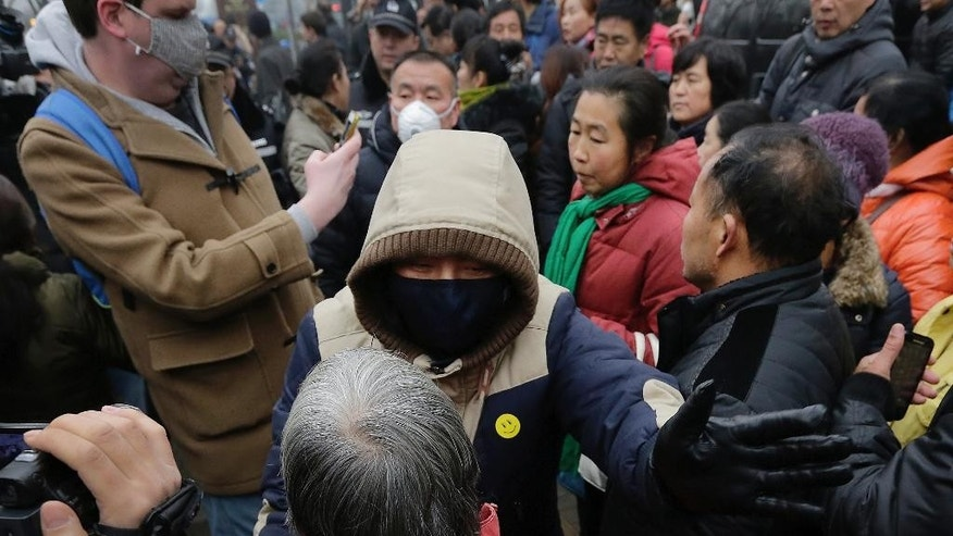 """In this Monday, Dec. 14, 2015, photo, a plainclothes policemen wearing a yellow smiley-face sticker urges supporters of rights lawyer Pu Zhiqiang to leave, near Beijing's No. 2 Intermediate Court in Beijing. The tough guys wore smiley face stickers, but they weren't there to spread good cheer. Scenes of pushing, shouting and shoving outside a Beijing courthouse this week were orchestrated by plainclothes security officers identified by a sticker familiar around the world — the yellow decal identified since the 1970s with the slogan """"Have a Nice Day."""" (AP Photo/Andy Wong)"""