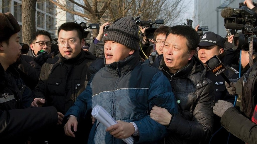 In this Jan. 26, 2014, file photo,  Zhang Qingfang, lawyer of legal scholar and founder of the New Citizens movement Xu Zhiyong, center, is taken away by policemen, one of them wearing a green sticker, as he speaks to the media near the No. 1 Intermediate People's Court in Beijing. The tough guys wore smiley face stickers, but they weren't there to spread good cheer. Ugly scenes of pushing, shouting and shoving outside a Beijing courthouse this week were orchestrated by plain clothes security officers identified with ironic flair by the familiar yellow decals associated with friendship and fun. (AP Photo/Andy Wong, File)