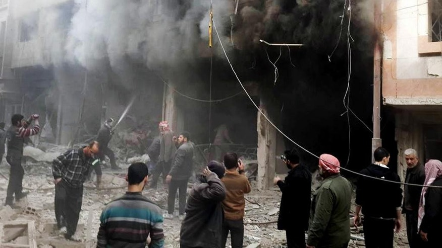This photo released on Sunday, Dec 13, 2015 by the Douma Revolution News Network on their Facebook page, shows Syrians trying to extinguish fire that was caused by Syrian government aerial bombardment on the Damascus suburb of Douma, Syria. Syrian government helicopter gunships have struck a suburb of the capital, Damascus, a day after airstrikes on nearby areas killed more than 40 people, opposition activists said. (Douma Revolution via AP)