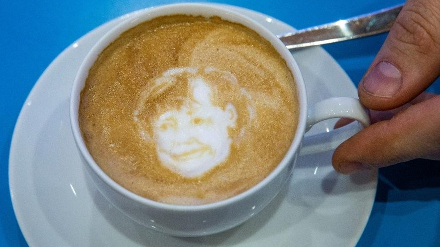 In this Dec. 14, 2015 photo the face of CDU federal chairwoman and Chancellor Angela Merkel has been etched into a cup of Cappuccino by a latte artist at the CDU (Christian Democratic Party) federal party congress in Karlsruhe, Germany. (Michael Kappeler/dpa via AP)
