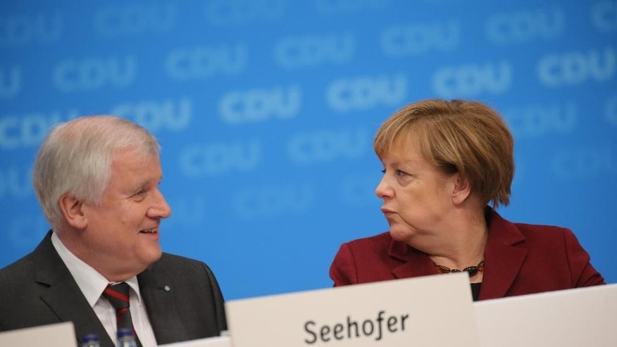 German Chancellor Angela Merkel greets Bavarian Governor Horst Seehofer during the CDU party conference in Karlsruhe, Germany, Tuesday, Dec. 15, 2015. Seehofer, Merkel's most prominent critic in the refugee crisis is sending conciliatory signals, welcoming her acknowledgement that an unabated influx would overburden Germany. (Michael Kappeler/dpa via AP)