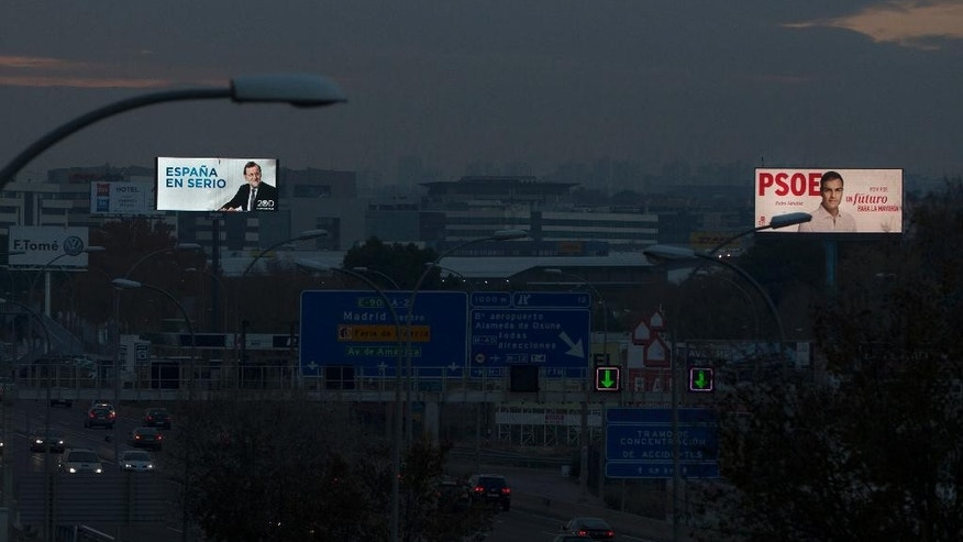 In this Tuesday, Dec. 8, 2015 photo, a giant poster of Spain's Prime Minister and Popular Party candidate Mariano Rajoy, left, and the main socialist opposition leader Pedro Sanchez, right, are displayed, close to a highway at the entrance of Madrid, Spain. The biggest difference between this weekend's crucial Spanish elections and ballots past: It's no longer a two-horse race. In less than two years, the business-friendly centrist group, Ciudadanos, and the hard left anti-austerity Podemos party have sprung up, gathered force and now pose a serious challenge to the ruling center-right Popular Party and the leading opposition Socialists _ who have alternated in office for nearly four decades. (AP Photo/Paul White)