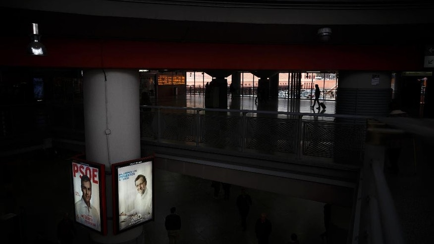 In this Saturday, Dec. 12, 2015 photo, posters showing images of Spanish Socialist party leader Pedro Sanchez, left, and Spain's Prime Minister and Popular Party candidate Mariano Rajoy, are displayed at Atocha train station in central Madrid. Spain. The biggest difference between this weekend's crucial Spanish elections and ballots past: It's no longer a two-horse race. In less than two years, the business-friendly centrist group, Ciudadanos, and the hard left anti-austerity Podemos party have sprung up, gathered force and now pose a serious challenge to the ruling center-right Popular Party and the leading opposition Socialists _ who have alternated in office for nearly four decades. (AP Photo/Daniel Ochoa de Olza)