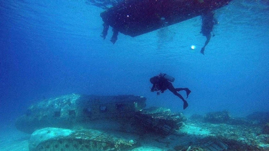 In this photo taken on Friday, Nov. 6, 2015, diver Hiroaki Ueda submerges below his boat as they explore a wrecked DC3 aircraft in the Majuro Atoll lagoon at the Marshall Islands. Diving in the Marshall Islands caters to all levels of skills from novice like this six-meter (20-foot) wreck dive to more complicated dives on World War ll ship wrecks using mixed gas. (AP Photo/Rob Griffith)