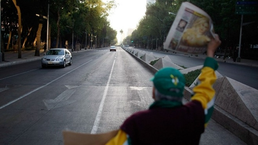 MEXICO CITY - MAY 01:  A newspaper vendor has few sales as vehicle traffic is light due to the beginning of a national holiday and the government advising people to stay home in hopes of containing the swine flu on May 1, 2009 in Mexico City, Mexico. Cases of swine flu, the strain known as H1N1 virus, have been confirmed in nine countries, including Mexico, where at least 2,400 are believed to be infected, with the number of deaths attributed to the virus believed to be more than 150. The World Health Organization today raised the threat level to 'phase 5,' indicating a 'pandemic is imminent.  (Photo by Joe Raedle/Getty Images)