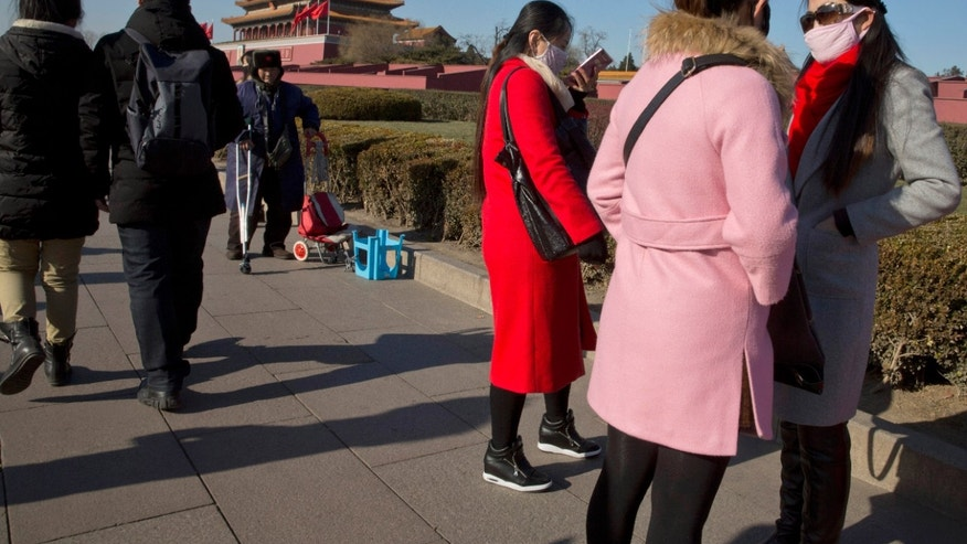 Dec. 18, 2015: Visitors to Tiananmen Gate wear masks during a blue sky day in Beijing. Residents in the Chinese capital are preparing for its second smog red alert as a wave of smog is forecasted to settle over the city from Saturday to Tuesday. (AP)