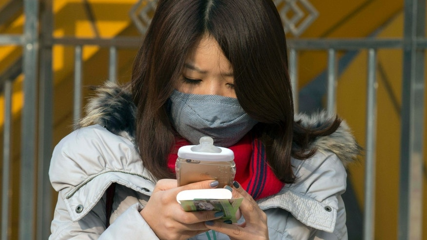 Dec. 19, 2015: A woman wears a mask during a polluted day in Beijing, China.
