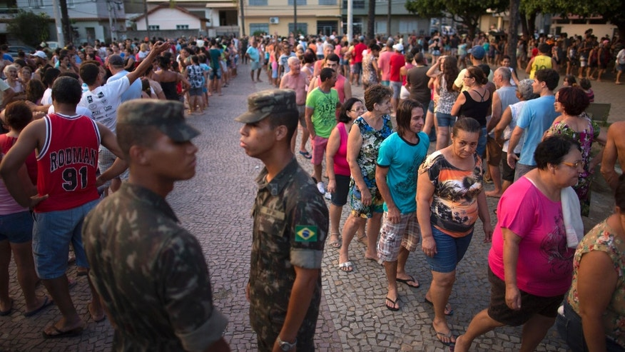 In this Nov. 21, 2015 photo, residents stand in line at a free water distribution site, weeks after a dam burst at the Samarco iron mine, causing mudslides and contaminated the area's drinkable water supplies, in Colatina, Brazil. The bottled water is provided by Samarco, which is jointly owned by mining giants Vale of Brazil and Australiaâs BHP Billiton. (AP Photo/Leo Correa)