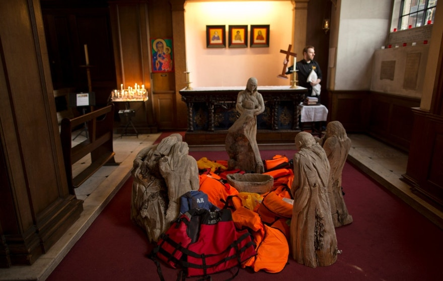Life jackets worn by refugees arriving by dinghy to the Greek island of Lesbos are displayed in the middle of the traditional nativity display next to a salvaged dinghy suspended in the nave forming an installation entitled 'Flight' by artist Arabella Dorman, at St James's Church, Piccadilly,   in London, Tuesday, Dec. 22, 2015. The boat is designed to carry 15 people, but transported 62 refugees, many from Syria, across 10km of rough sea from Assos, Turkey, to Lesbos in Greece, with all onboard surviving the journey. (AP Photo/Matt Dunham)