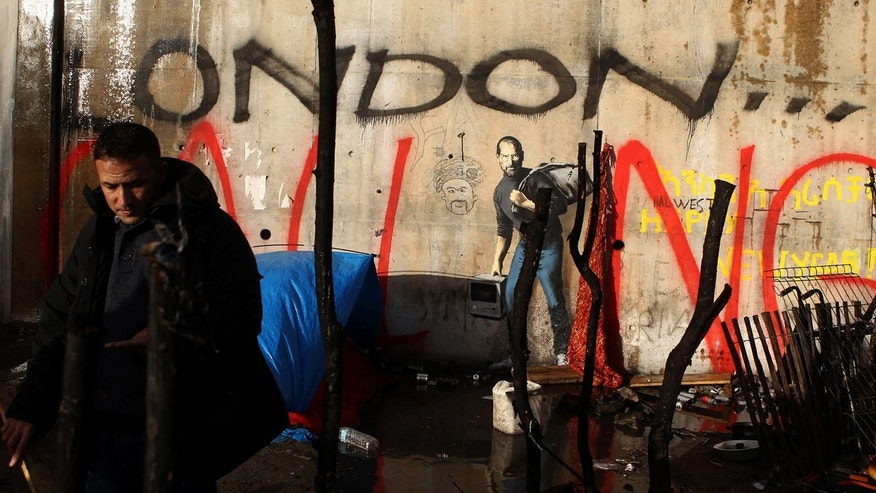 Dec. 21, 2015: A painting by English graffiti artist Banksy is seen at the entrance of the Calais refugee camp in France, in Calais, northern France.The elusive graffiti artist has depicted the late Apple guru Steve Jobs --— whose biological father was from Syria --— carrying a black garbage bag and an early model of the Macintosh computer. (AP Photo/Michel Spingler)