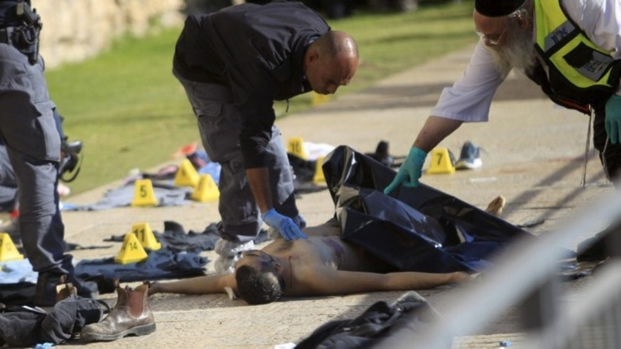 Dec. 23, 2015: An Israeli forensic policeman and an emergency service employee work next to the body of a Palestinian, who was shot dead by Israeli police after he went on a stabbing spree along with another Palestinian man, wounding at least three people, in what authorities called a terrorist attack, near Jaffa Gate in Jerusalem's Old City. (Reuters)