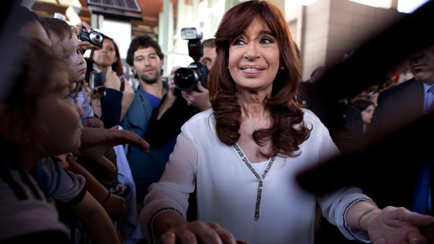 FILE - In this Nov. 6, 2015 file photo, Argentina's President Cristina Fernandez greets supporters after a ceremony with presidential candidate Daniel Scioli, her chosen successor, outside the Science and Technology Center, in Buenos Aires, Argentina. When Argentines chose a new president in recent elections, many voters seemed more concerned about what would happen with the old one. Such is the hold of Fernandez on the public imagination in this South American country, where the combative and polarizing leader steps down Dec. 10 after dominating the political landscape during eight years in office. (AP Photo/Natacha Pisarenko, File)