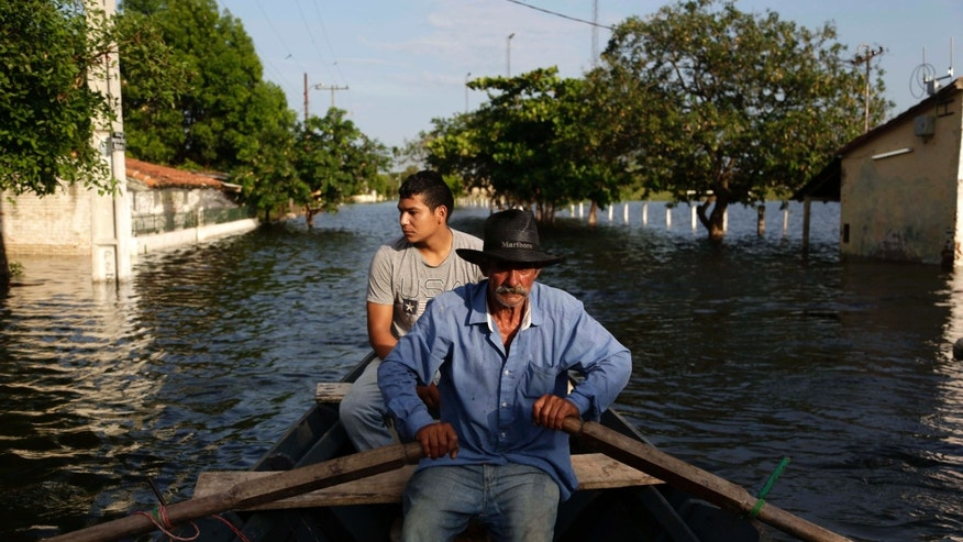 Victor Ferreira, who is displaced by flooding, rows his boat through the streets of his Jukyty neighborhood in Asuncion, Paraguay, Wednesday, Dec. 23, 2015. The Paraguay River is at its highest level since 1984 and threatening the poor districts that surround the capital, forcing about 100,000 people to shelters. (AP Photo/Jorge Saenz)