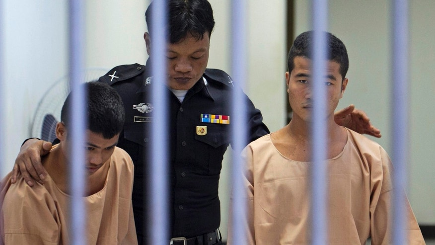 Dec. 24, 2015: Myanmar migrants Win Zaw Htun, right, and Zaw Lin, left, both 22, are escorted by an official after their guilty verdict at court in Koh Samui, Thailand.