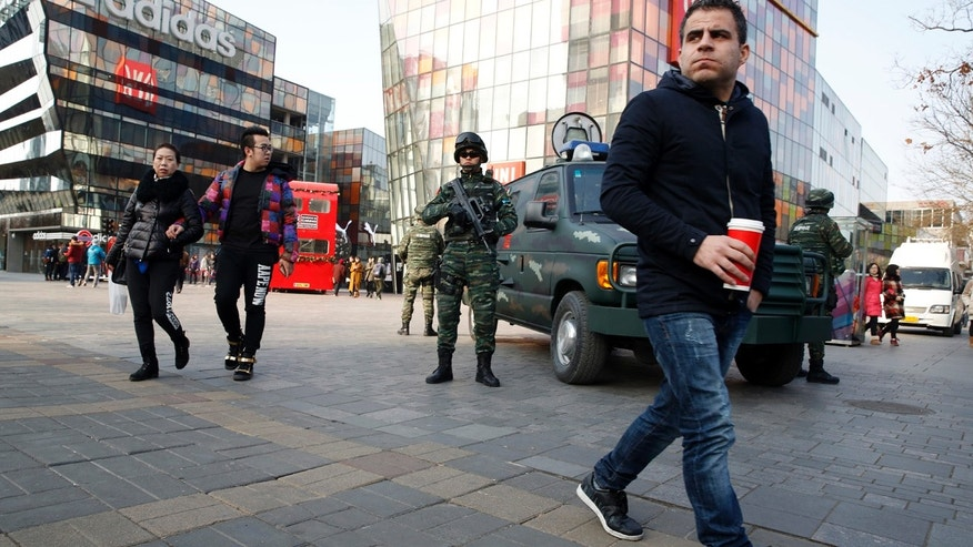 Heavily armed Chinese paramilitary police guard a popular mall in the Sanlitun district of Beijing, China, Thursday, Dec. 24, 2015. Increased security could be seen in the area as the U.S. and British embassies in the Chinese capital issued travel alerts regarding the possible threats against westerners in the Sanlitun area. (AP Photo/Ng Han Guan)