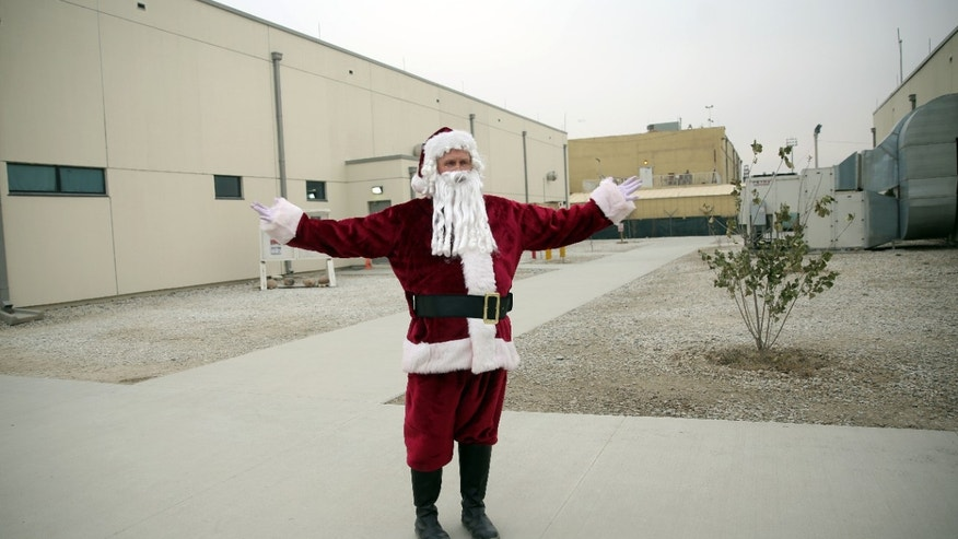 "A U.S. soldier dressed up as Santa Claus says ""Merry Christmas"" to journalists, during Christmas day celebrations at Bagram Air Field, north of Kabul, Afghanistan, Friday, Dec. 25, 2015. (AP Photo/Massoud Hossaini)"